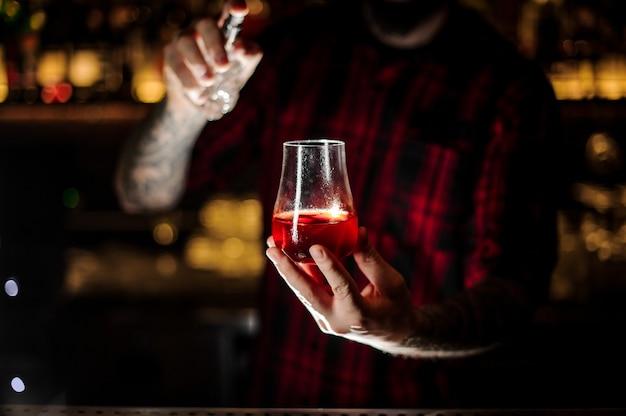 Barman tatuado espalhando amargo no copo com coquetel doce vermelho fresco no balcão do bar