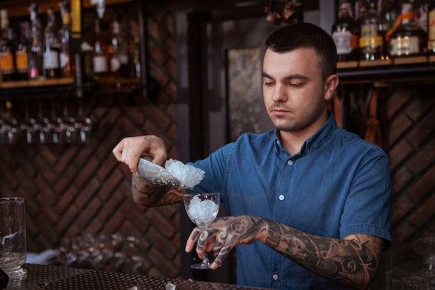 Barman tatuado homem bonito, preparando uma bebida