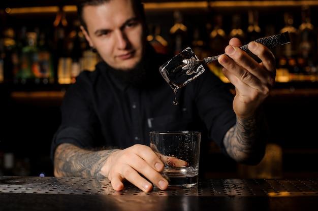 Barman tatuado jovem colocando um cubo de gelo em um copo de coquetel