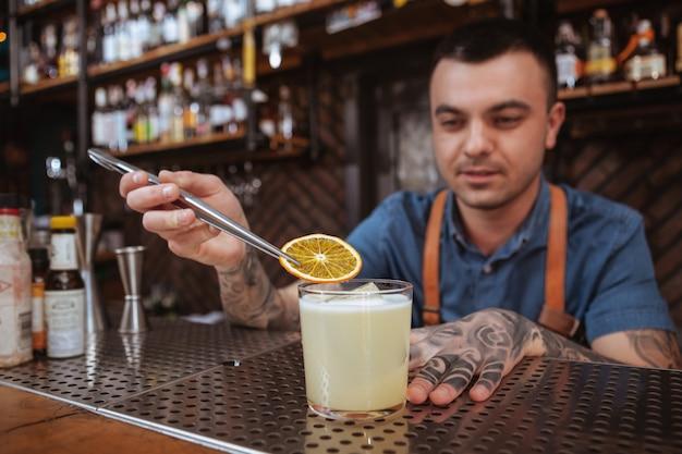 Barman tatuado masculino bonito, preparando uma bebida