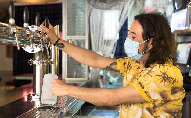 Barman tatuado servindo uma jarra de cerveja.