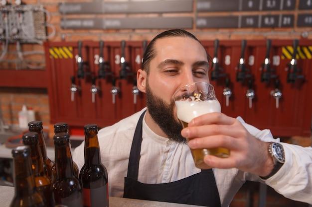 Barman tomando uma cerveja deliciosa, fechando os olhos de prazer