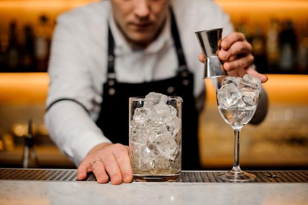 Barman, vestido com uma camisa branca com um copo com cubos de gelo