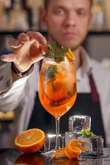 Barmen está fazendo um cocktail aperol spritz