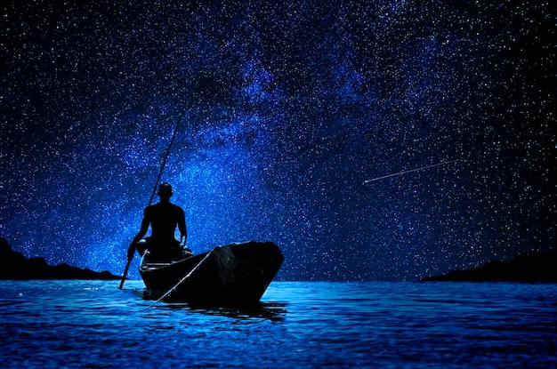 Barqueiro africano com sua canoa na frente das estrelas