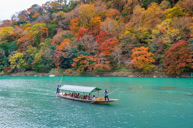 Barqueiro rebatendo o barco no rio. arashiyama na temporada de outono ao longo do rio em kyoto, japão