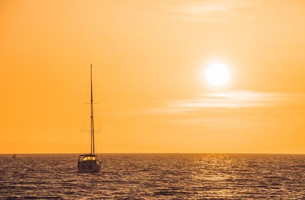 Barquinho branco flutuando na água em direção ao horizonte ao pôr do sol