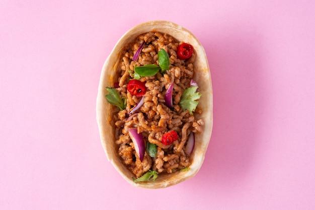 Barquita taco mexicano com carne, pimenta, tomate, cebola e especiarias isoladas em um fundo rosa