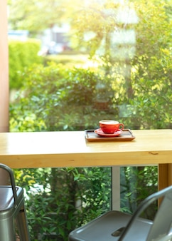 Barra contrária de madeira e cadeiras pretas perto do vidro de janela no café com café no copo vermelho.