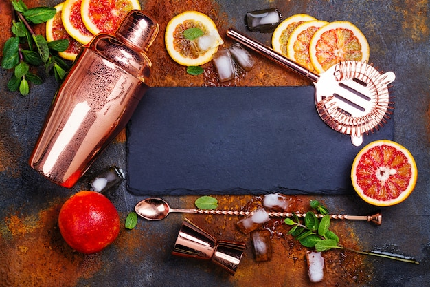 Barra de acessórios, ferramentas de bebidas e coquetel ingredientes na mesa de pedra enferrujada.