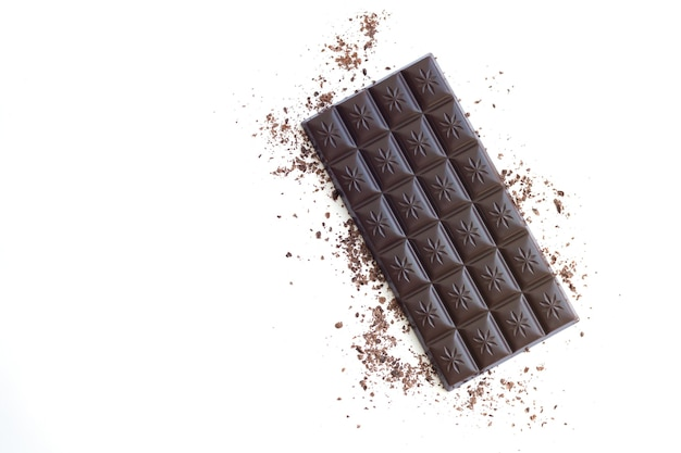 Barra de chocolate amargo com aparas de vista superior isolada com espaço de cópia