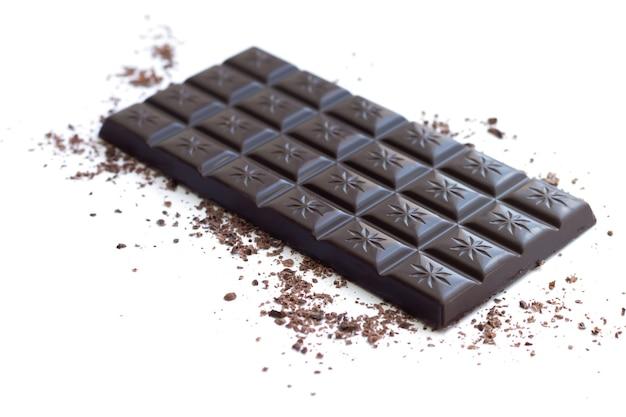 Barra de chocolate amargo com aparas e pó isolado na superfície branca