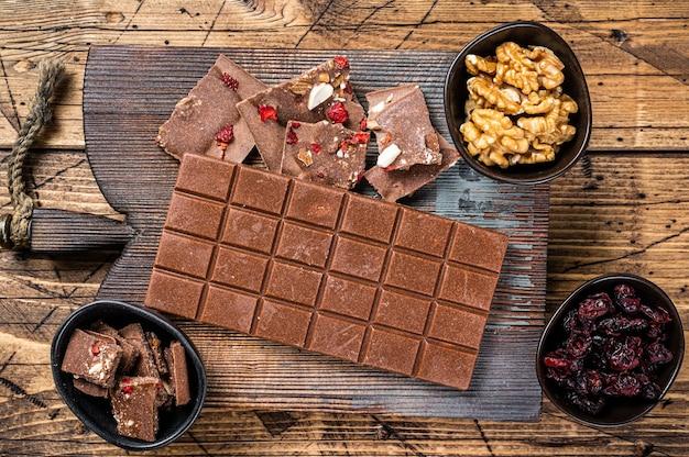 Barra de chocolate amargo com avelãs, amendoins, cranberries e framboesas liofilizadas em uma placa de madeira. fundo de madeira. vista do topo.