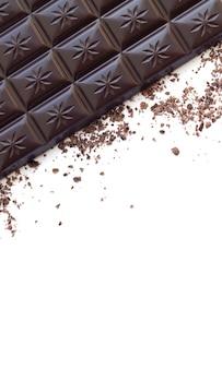 Barra de chocolate amargo com vista superior das aparas isolada na superfície branca, foto vertical