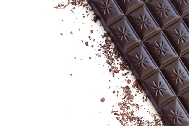 Barra de chocolate amargo com vista superior das aparas isolada na superfície branca