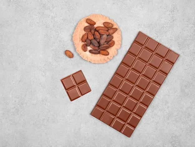 Barra de chocolate ao leite e grãos de cacau em fundo de pedra cinza vista superior com espaço de cópia