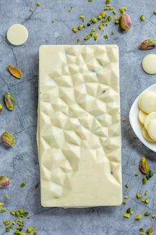 Barra de chocolate branco artesanal com pistache e framboesas secas no fundo brilhante. vista do topo.