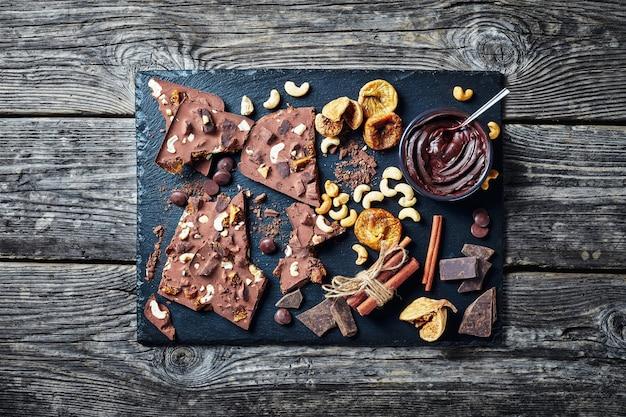 Barra de chocolate caseiro com figos secos e recheio de caju em uma bandeja de pedra preta com ingredientes, vista horizontal de cima, flatlay