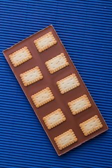 Barra de chocolate com biscoitos crocantes sobre fundo azul.