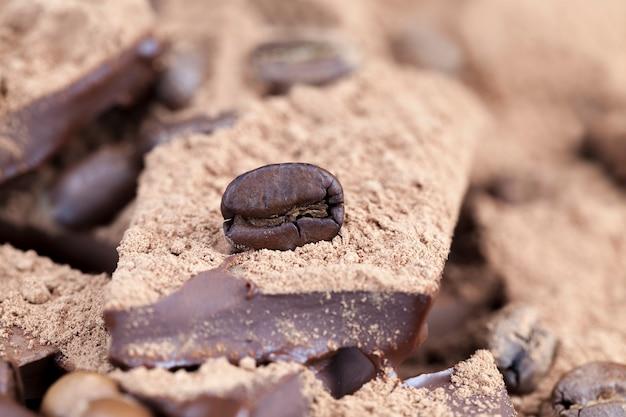 Barra de chocolate com cobertura de cacau em pó e grãos de café, close-up de comida de cacau, foto com ingredientes de lazer - cacau e café