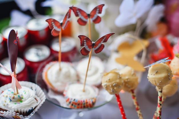 Barra de chocolate com cupcakes e pirulitos decorados com borboletas