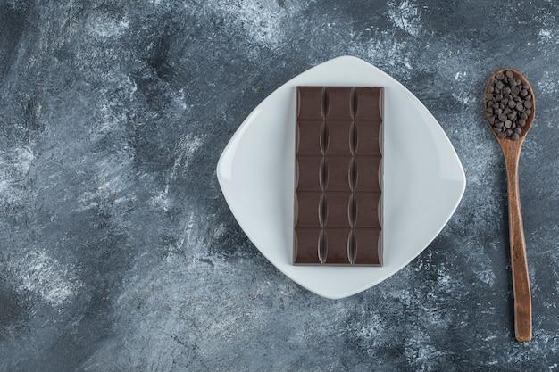 Barra de chocolate com gotas de chocolate numa superfície de mármore.