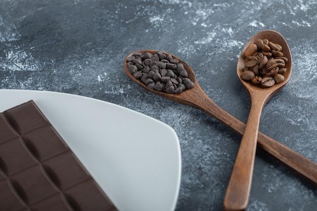 Barra de chocolate com grãos de café e gotas de chocolate.