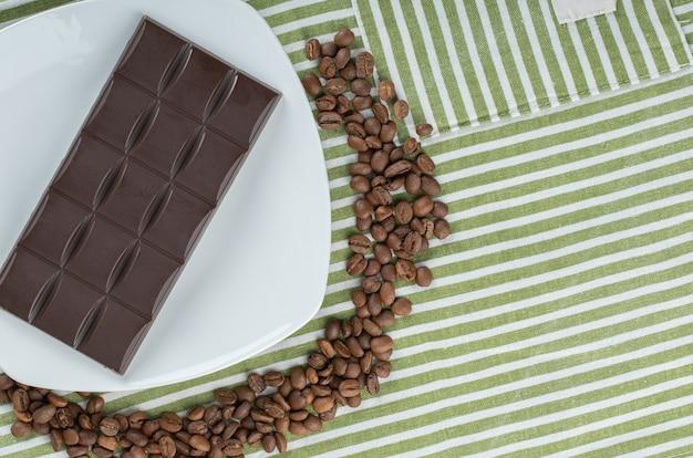Barra de chocolate com grãos de café sobre uma toalha de mesa.