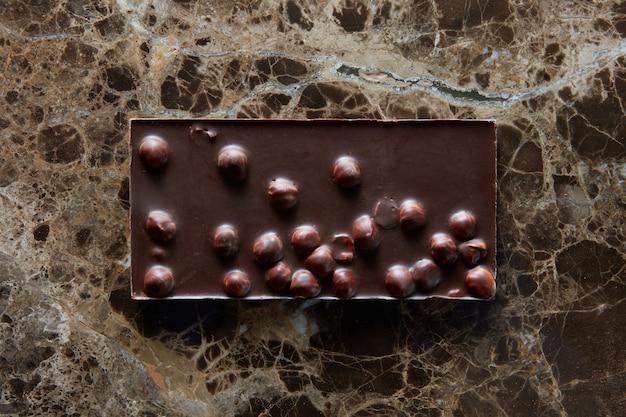 Barra de chocolate com nozes em uma superfície escura de um mármore.