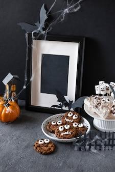 Barra de chocolate de halloween: monstros engraçados feitos de biscoitos com chocolate e close-up de marshmelow fantasmas em cima da mesa