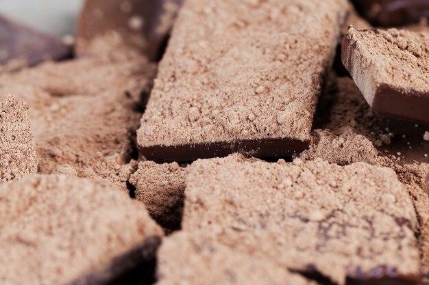 Barra de chocolate doce quebrada em pedaços com granulado de cacau