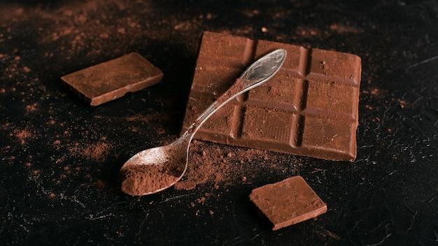Barra de chocolate e colher com cacau em pó