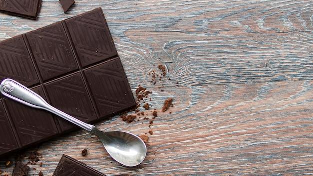 Barra de chocolate e colher de chá de prata na mesa de madeira gasto