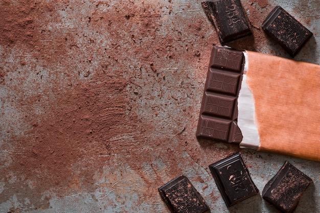 Barra de chocolate e pedaços com cacau em pó no cenário rústico