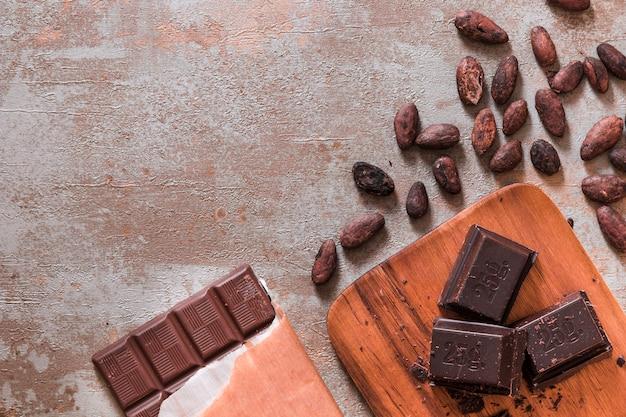 Barra de chocolate e pedaços com grãos de cacau no pano de fundo rústico