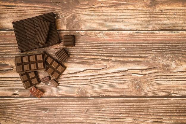 Barra de chocolate e pedaços na mesa de madeira