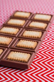 Barra de chocolate em close up shot vertical com biscoitos crocantes