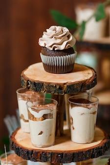 Barra de chocolate em festa de casamento de madeira com muitos doces diferentes, suflê de cupcakes e bolos