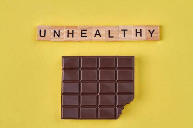 Barra de chocolate em fundo amarelo. conceito de alimentos pouco saudáveis.