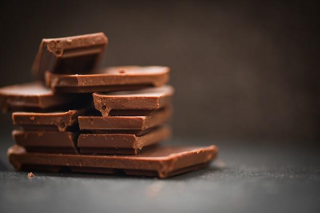 Barra de chocolate empilhada sobre o fundo escuro pedaços de chocolate