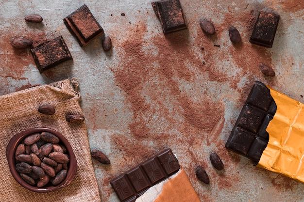 Barra de chocolate escuro com pó de cacau e tigela de feijão
