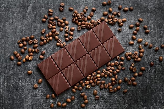 Barra de chocolate espalhada por grãos de café, preto, vista de cima