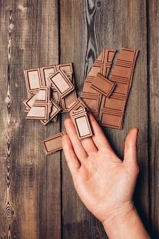 Barra de chocolate na mão e mesa