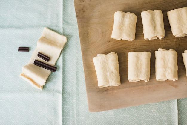 Barra de chocolate na massa folhada crua dobrada disposta na tábua de cortar madeira