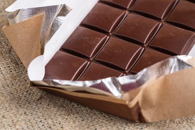 Barra de chocolate no invólucro de papel na serapilheira