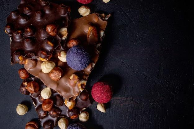 Barra de chocolate, pedaços triturados de chocolate amargo e nozes. doces de chocolate praliné. copie o espaço.