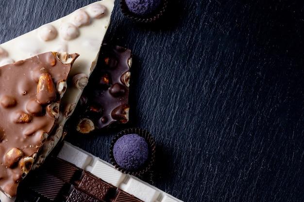 Barra de chocolate, pedaços triturados de chocolate amargo e nozes. doces de chocolate praliné