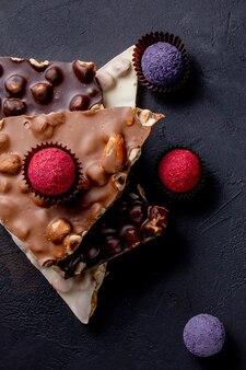 Barra de chocolate, pedaços triturados de chocolate amargo e nozes. doces de chocolate praliné.