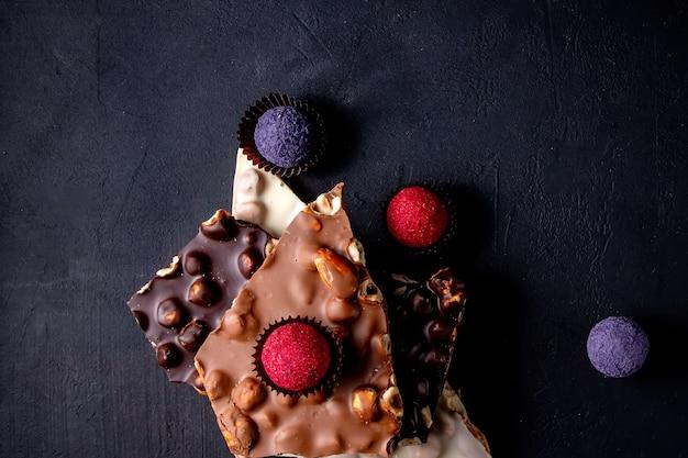 Barra de chocolate, pedaços triturados de chocolate preto e nozes. doces de chocolate praliné.