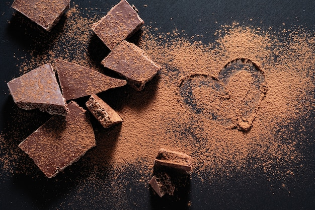 Barra de chocolate quebrada em um fundo preto, cacau em pó pintado coração